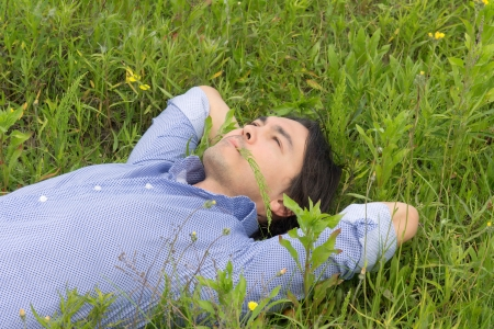 young man lying on the grass with his hands behind his head photo