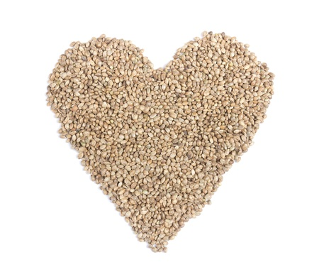 Hemp seeds in heart shape on white background. Stock Photo