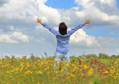 Young man standing on a spring meadow with raised hands photo