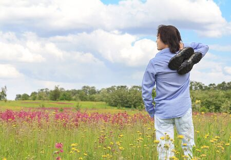 Young man standing on a spring meadow holding sneakers in his hands photo