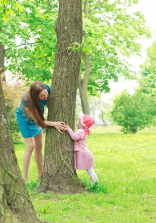 Woman and child playing hide and seek in spring park Standard-Bild