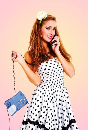 classical pin-up image of young beautiful girl talking on the phone. Toned in retro style. photo