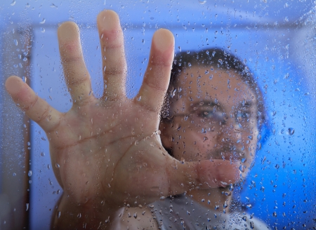 young adult man looking through the window on a rainy day. focus on the raindrops on the glass photo