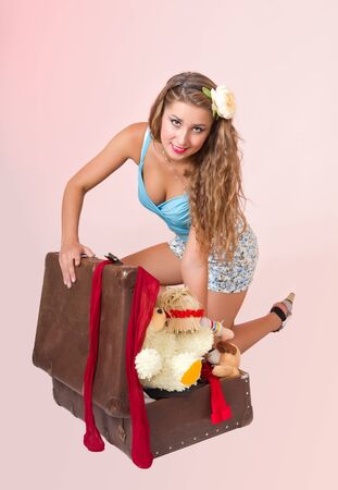 young fashion travel pin up girl closing suitcase, on pink background photo