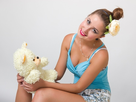 Beautiful young pin up girl hugging teddy bear photo
