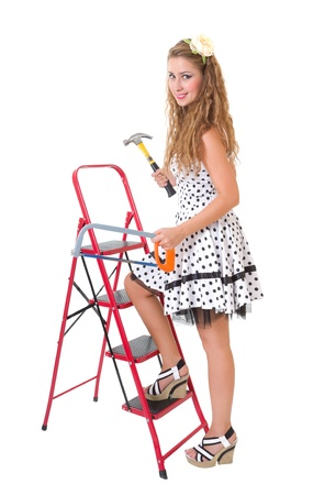 Pretty young pin up woman on a ladder with a hammer and saw, isolated on white background photo