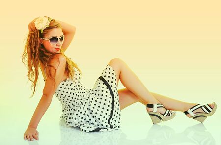 pretty young happy pin up woman in sunglasses sitting in studio, toned in retro style photo