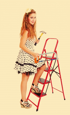 Pretty young pin up woman on a ladder with a hammer and saw, toned in retro style photo