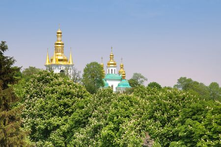 The domes of Peshtersk Lavra - a shot from behind the trees, Kyiv, Ukraine photo