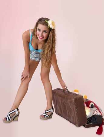 Sexy pin up woman pulling vacation suitcase, on pink background photo