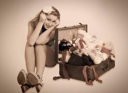 Beautiful pin up woman sitting near her vacation suitcase, toned in retro style photo