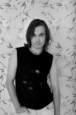 Monochrome portrait of handsome brunet man casually leaning against the pattern wall photo