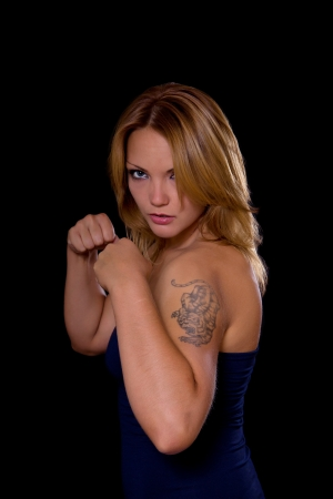 Low key image of angry tattooed caucasian woman with fists clenched on black background photo