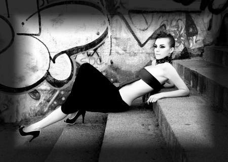 Beautiful cyber futuristic woman near graffiti wall, monochrome photo