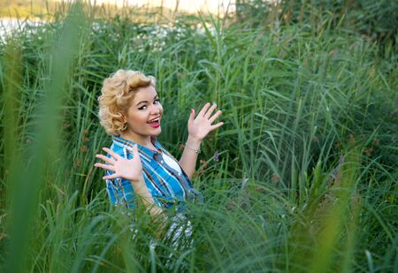 beautiful happy surprised pinup girl standing alone at green grass photo
