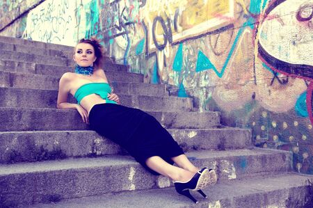 Beautiful futuristic fashion model lying on steps photo