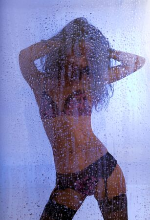Young sexy woman standing under rain with her hands on head