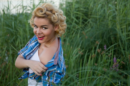 Young blond pinup female taking off her shirt Stock Photo - 15287524