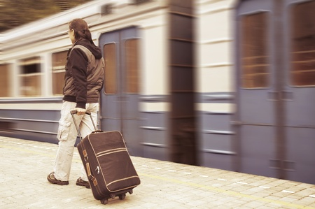 Young man with a baggage on the platform of a train station photo