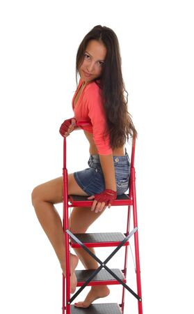 Portrait of a beautiful young woman sitting on a ladder, isolated on white background. photo