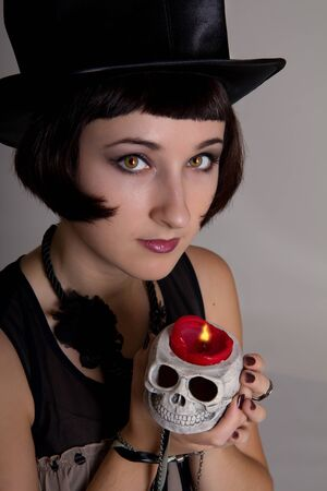Pretty Halloween witch with a skull in a black cylinder hat with fire reflection in her eyes photo