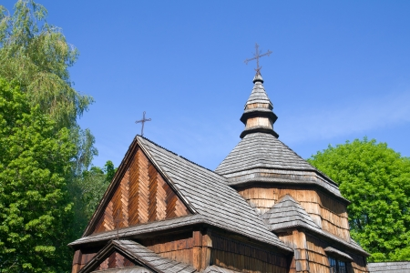 Spring landscape with wooden orthodox church and blue sky photo