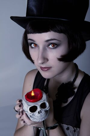 Pretty Halloween vampire girl with a skull in a black cylinder hat with fire reflection in her eyes photo