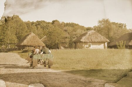 People sitting in the wooden cart in field, image toned in retro style photo