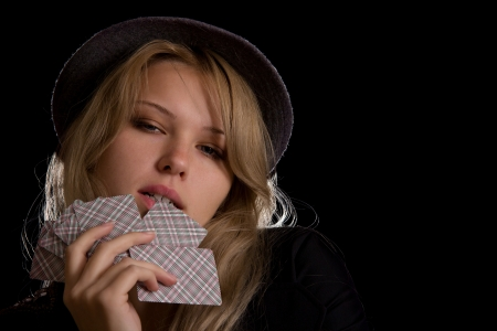 pretty blond woman in hat biting poker cards on black background Stock Photo