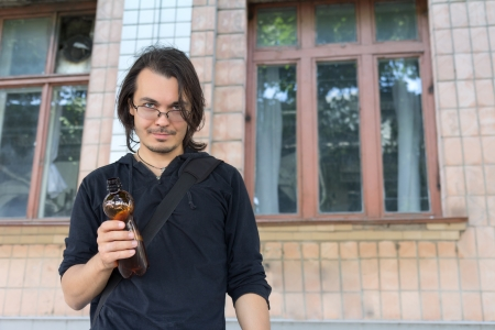 portrait of a young drunk  man holding  plastic bottle photo