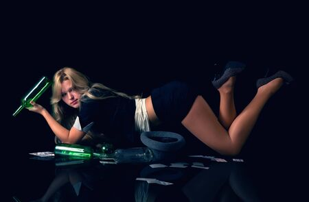 Beutiful blond woman lying on floor holding empty bottle of wine and playing cards photo