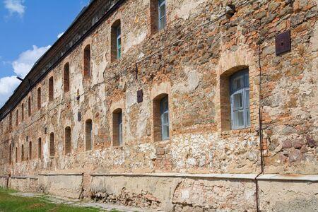 Old orange brick wall with windows in Monastery - Fortress of Carmelites, Berdychiv, Zhytomyr Region, Ukraine photo