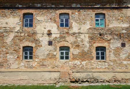 Old orange brick wall with six windows in Monastery - Fortress of Carmelites, Berdychiv, Zhytomyr Region, Ukraine photo