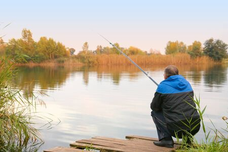 Rear view of senior man fishing on the lake Stock Photo - 16411029