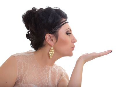 beautiful young brunette woman blowing a kiss, isolated on white background photo
