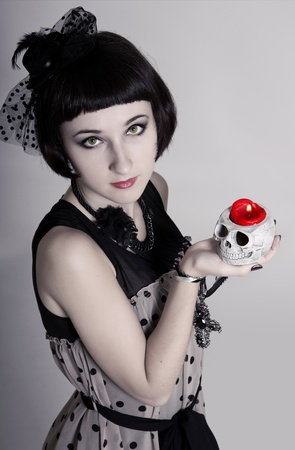 Beautiful vampire woman with green eyes and a skull in her hands photo