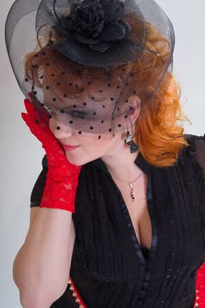 Closeup portrait of a young woman with red hair in black hat with net veil and red gloves Stock Photo - 16715482