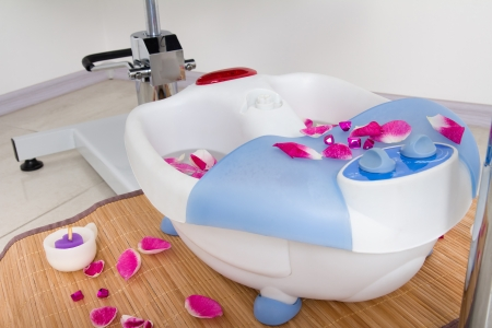 electric foot spa with flower petals on a bamboo mat Stock Photo