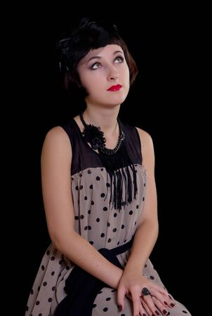 Portrait of beautiful woman in retro styled dress on black background photo