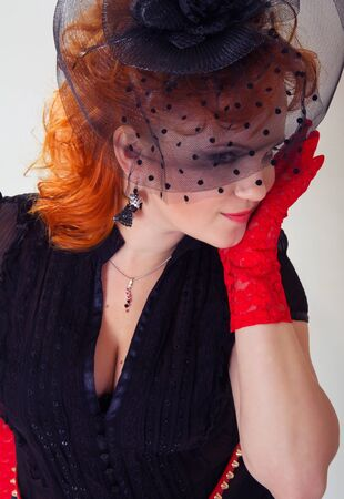 Portrait of a young woman with red hair in black hat with net veil and red gloves in retro style Stock Photo - 16826373