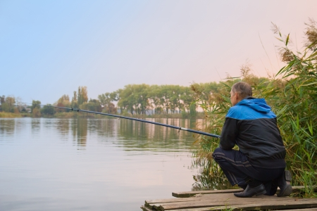 Rear view of senior man fishing on the lake Stock Photo - 16963280