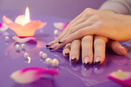 Woman hands with french manicure with crystals and rose petals Standard-Bild