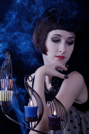 portrait of a beautiful witch with a candles and blue smoke on a black background photo