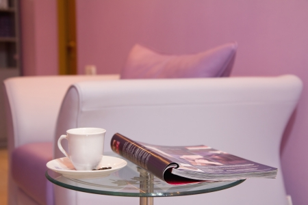 Purple leather sofa, cup of coffee and a magazine at waiting room.