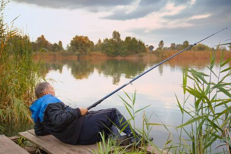 Rear view of senior man fishing on the lake Stock Photo - 17051645