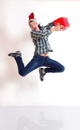 Funny young man in santa cap in hurry running or jumping with gifts  Stock Photo - 17051631