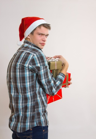 Unhappy disappointed greedy young man - Santa Claus holding gift boxes photo