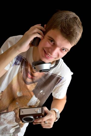Happy young man in phones with an old radio. Over black background Stock Photo - 17134515