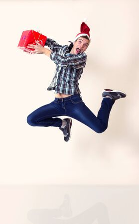 Happy young man in santa cap in hurry running or jumping with gifts Stock Photo - 17134506