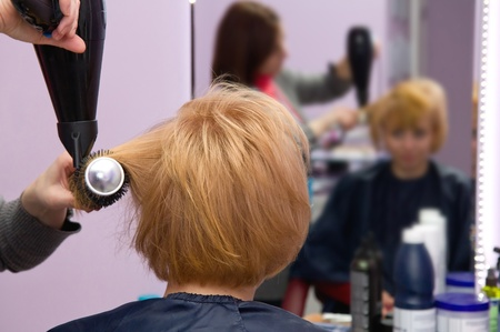 Hairdresser drying womans hair in beauty salon photo